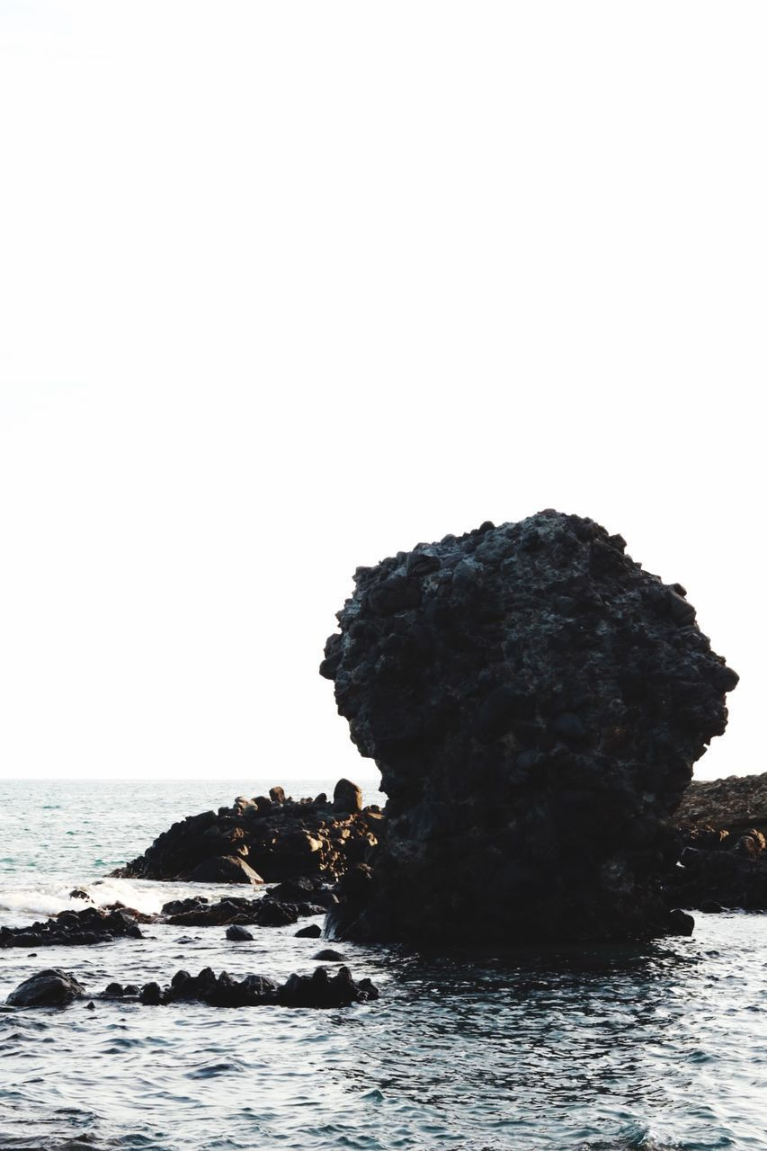 ROCKS ON SEA AGAINST CLEAR SKY