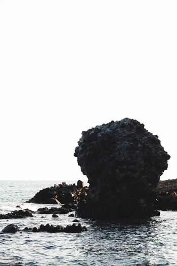 Rock formation in sea against clear sky