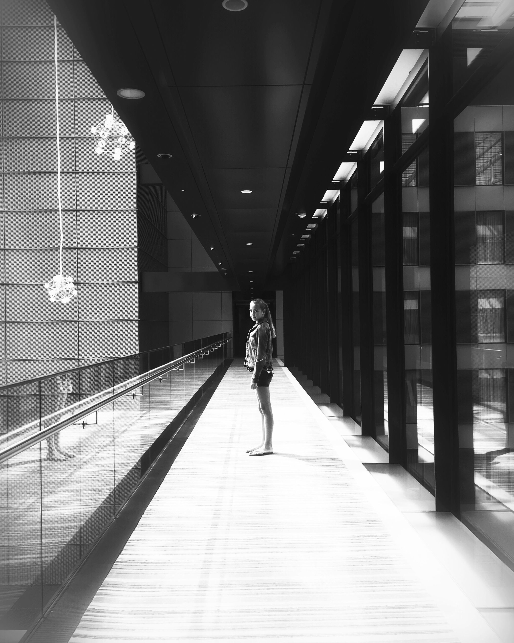 full length, indoors, architecture, walking, built structure, lifestyles, rear view, the way forward, corridor, men, person, leisure activity, casual clothing, city life, diminishing perspective, modern, ceiling, building
