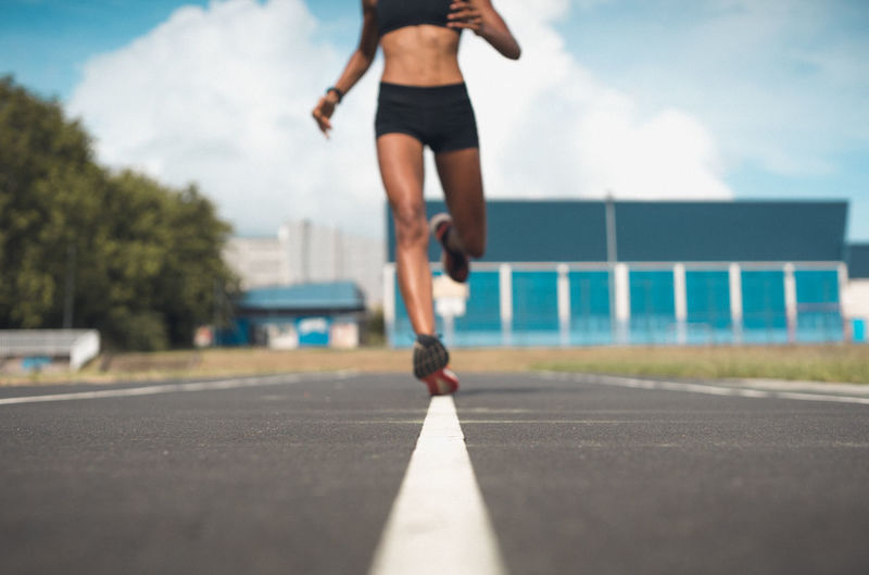 Low Section Of Woman Running On Road Against Sky