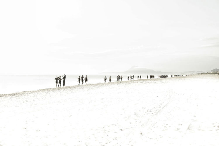 Group of people on beach against sky