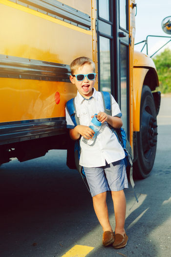 Full length portrait of boy leaning on bus while standing on road