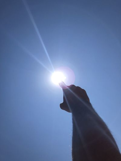 Low angle view of hand against bright sun