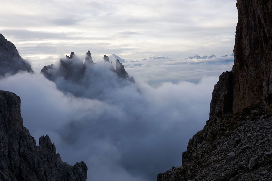 Like rocks among the waves: the Castello di Vedorcia emerges from a sea of clouds while descending from Campanile Toro. Cloudscape Dolomites, Italy Spalti Di Toro Beauty In Nature Cloud - Sky Clouds And Sky Dolomiti Landscape Mountain Nature Outdoors Sky Towers Tranquil Scene Tranquility