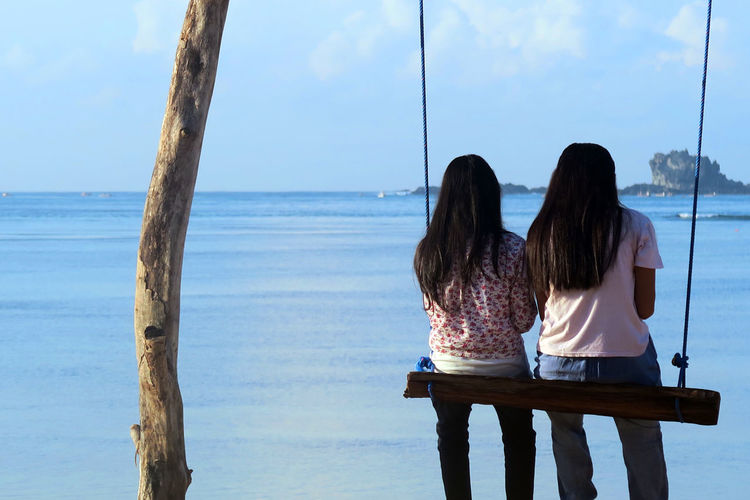Rear view of girls sitting on beach against sky