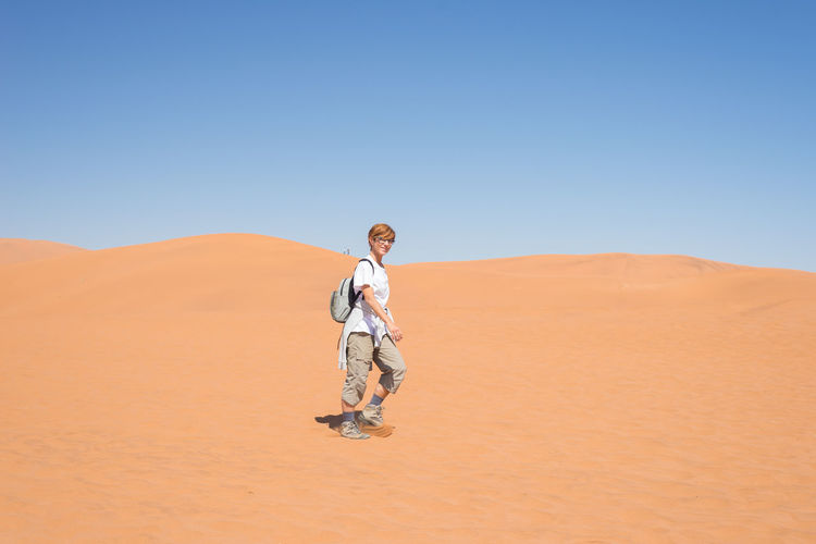 Tourist walking on sand dune at namib-naukluft national park