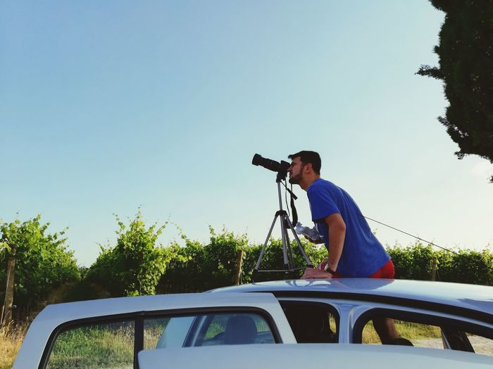 Side view of man photographing on car roof against blue sky