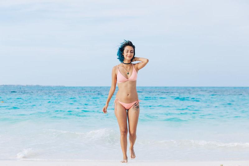 Full Length Of Smiling Woman In Bikini Standing At Beach Against Sky