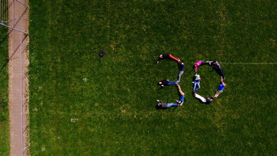 High angle view of people forming number 30 on grassy field