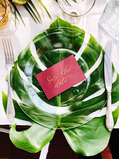 Save the date card on a plate for a wedding dinner Groom Bride Wedding Invitation Wedding Reception Save The Date Still Life Wedding Photography Wedding Green Color Indoors  High Angle View No People Leaf Close-up Plant Part Celebration Freshness Still Life Food Food And Drink Table Plant EyeEmNewHere