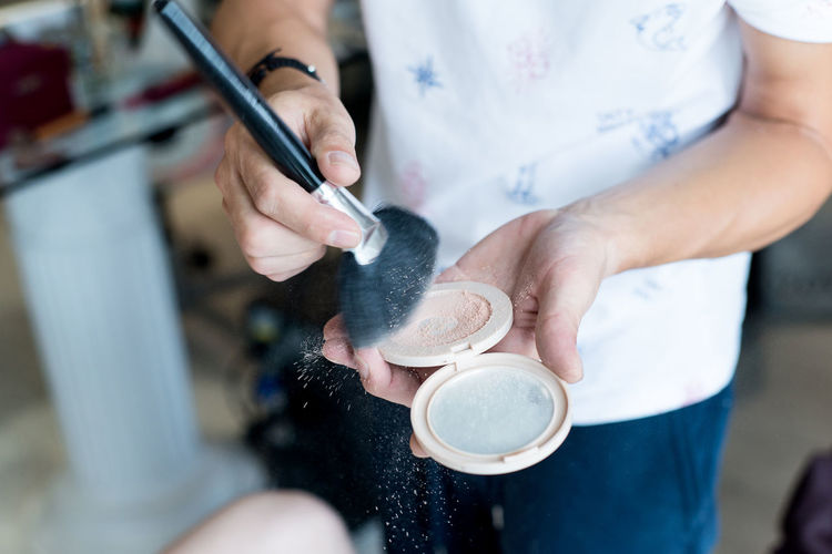 Midsection of make-up artist holding compact powder and brush