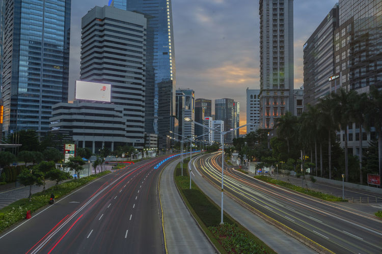 Panoramic view of road amidst buildings in city against sky