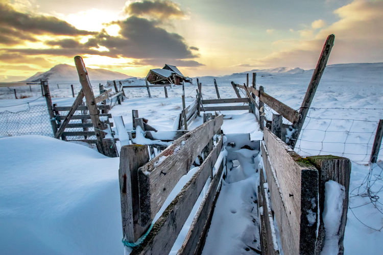 The frozen shed Iceland Jason Gines Barrier Beauty In Nature Cloud - Sky Cold Temperature Covering Field Frozen Land Nature No People Outdoors Scenics - Nature Shed Sky Snow Snowcapped Mountain Sunset Tranquil Scene Tranquility Water Winter Wood - Material Wooden Post