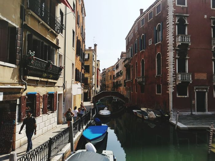 People on canal amidst buildings in city