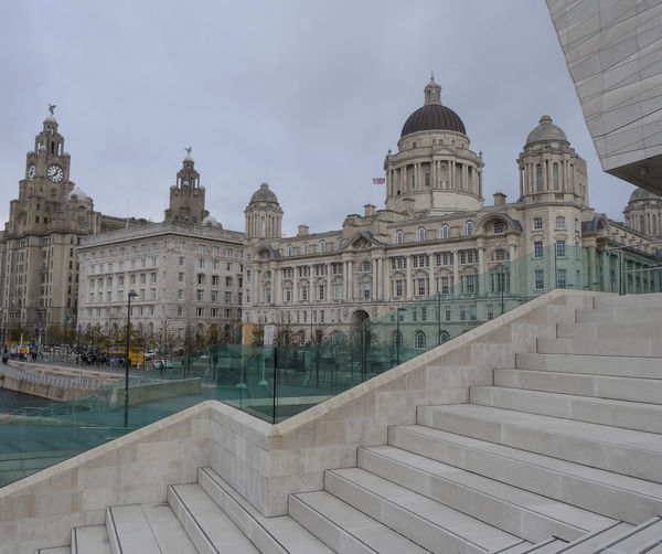 🌼 Liverpool UK and her Three Graces consisting of the Royal Liver Building, The Cunard Building and the Port of Liverpool Building. This iconic waterfront is viewed from the steps of The Museum of Liverpool. 🌼 Liverpool UK und ihre drei Grazien, bestehend aus dem Royal Liver Building, dem Cunard Building und dem Hafen von Liverpool Building. Diese ikonische Uferpromenade wird von den Stufen des Museums von Liverpool aus gesehen.🌼 Liverpool UK e le sue tre grazie consistenti del Royal Liver Building, The Cunard Building e il Port of Liverpool Building. Questo iconico lungomare è visto dai gradini del Museo di Liverpool. Liverpool, England Liverpool Waterfront Iconic Buildings Famous Places Liver Birds Clock Face Union Jack Places I Love Favorite Places UNESCO World Heritage Site Politics And Government City Dome History Architecture Built Structure Steps And Staircases Hand Rail Staircase Parliament Building Civilization Stairway Steps Government Building