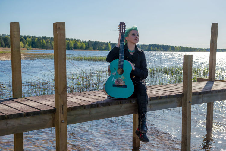 A musician with blue hair and a blue guitar sits on a lake footbridge and plays music. Girl Woman Guitar Guitarist Musician Lifestyle Blue Blue Hair Blue Guitar Street Instrument Artist Female Casual Pensive Performer  Adult Singer  Solitude Outdoors Fashion Coustic Guitar person Playing Clothing Water Lake Sea Footbridge Relaxing Wood - Material One Person Casual Clothing Leisure Activity Nature Day Real People Lifestyles Full Length Young Adult Sky Pier Sitting Front View Young Women Wooden Post