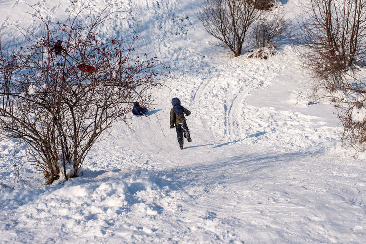Child running down a snow track, while having fun in the park.