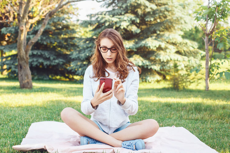 Young woman using mobile phone while sitting on grass