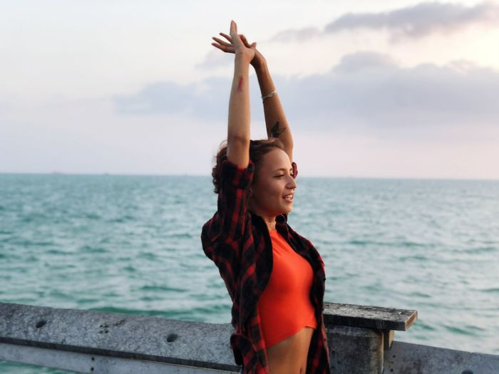 Beautiful Woman With Arms Raised Standing On Pier By Sea