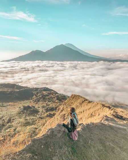 Woman Sitting On Mountain Against Cloudscape