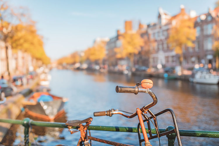 Close-up of bicycle by canal and buildings