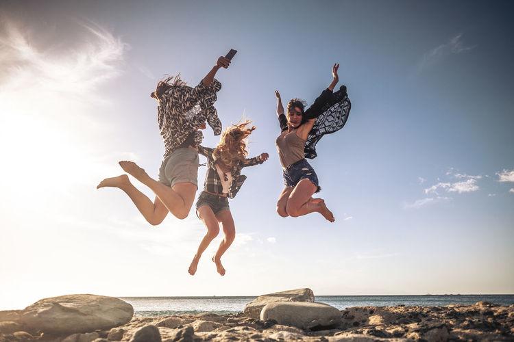 Cheerful friends jumping on beach against sky