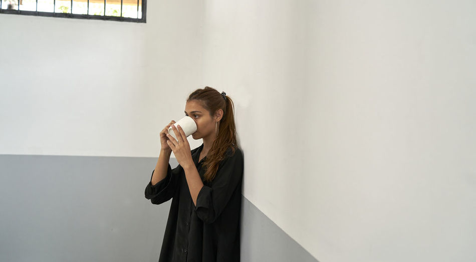 Young woman drinking water from coffee cup against wall