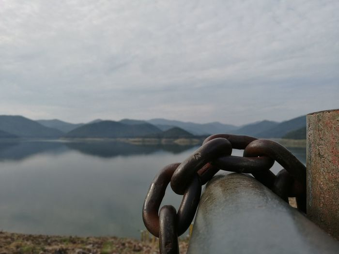Close-up of chain on metal against lake