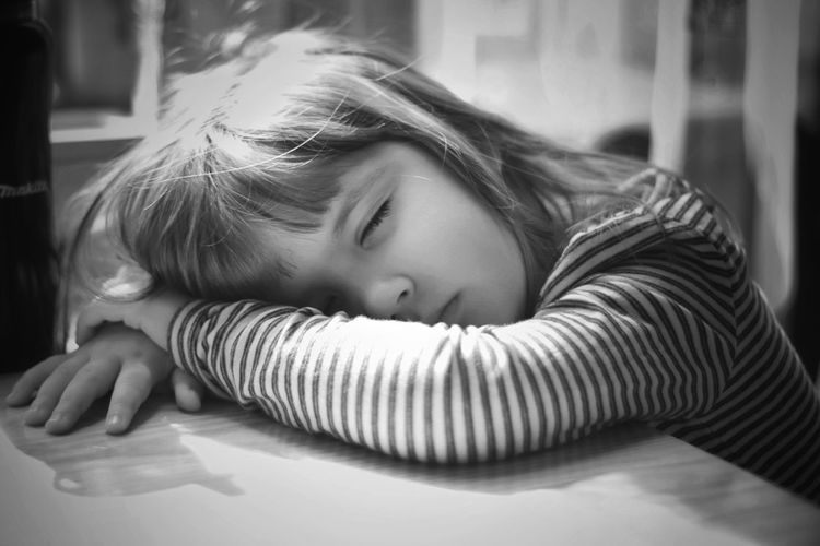 Close-up of girl lying on table at home