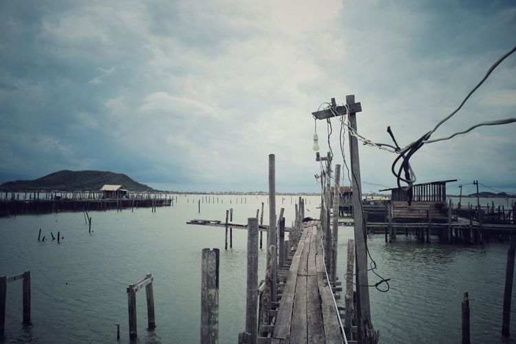Old wooden walkway on the coast at the traditional fish farm with cloudy sky and island background