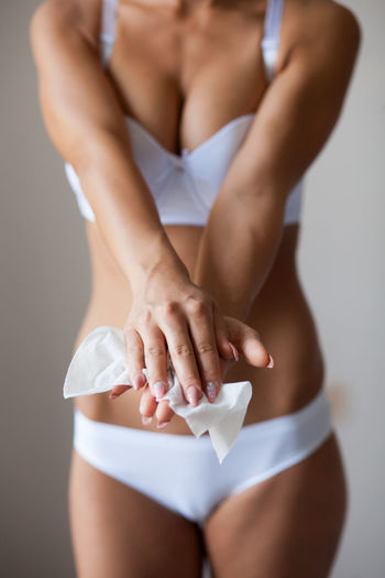 Midsection of woman cleaning fingers with tissue paper against gray background