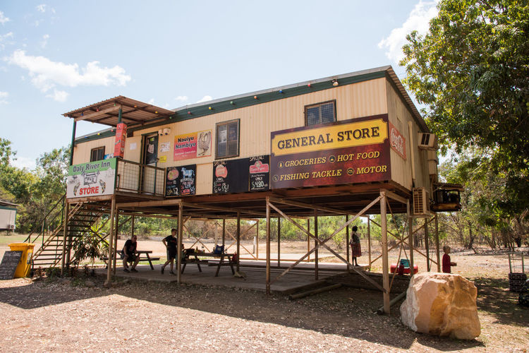 Daly, Northern Territory, Australia-September 15,2018: General Store in the Daly River area with tourists picnicking underneath surrounded by bushland in the Northern Territory of Australia Text Nature Architecture Communication Sky Built Structure Tree Western Script Building Exterior Outdoors Northern Territory Daly Australia Vacations Holiday Trip People Tourists Tourism Tourism Destination Travel Travel Destinations Tropical Trailer Elevated Picnic Table Picnic Picnicking Incidental People Family Vacation Break Rest Stop Sign General Store Store Staircase Bushland Forest Sand Remote Location Shop Rural Scene Non-urban Scene Building Supplies Resting Taking A Break Road Trip Placard Advertisement