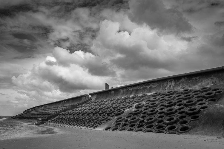 Retaining wall at beach against cloudy sky