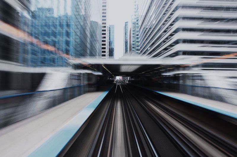 Blurred motion of railroad station amidst buildings in city