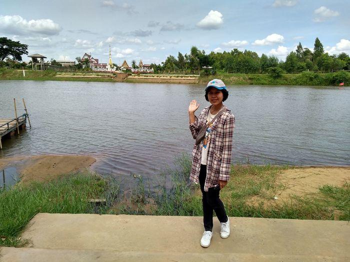 Full length of boy standing on lake against sky