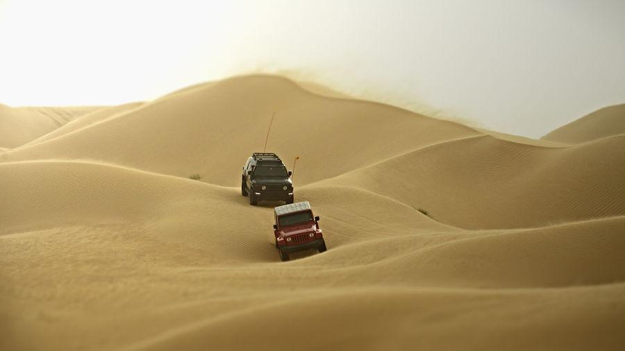 Vehicles On Sand Dunes In Desert Against Sky