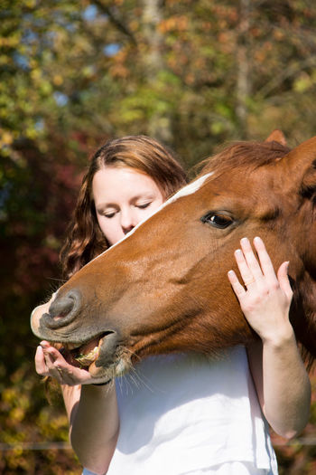 Young woman stroking horse at farm