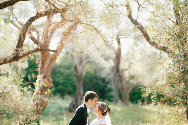Man kissing bride in forest