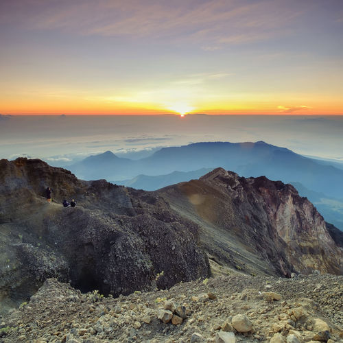 People sitting on summit mount rinjani at sunset