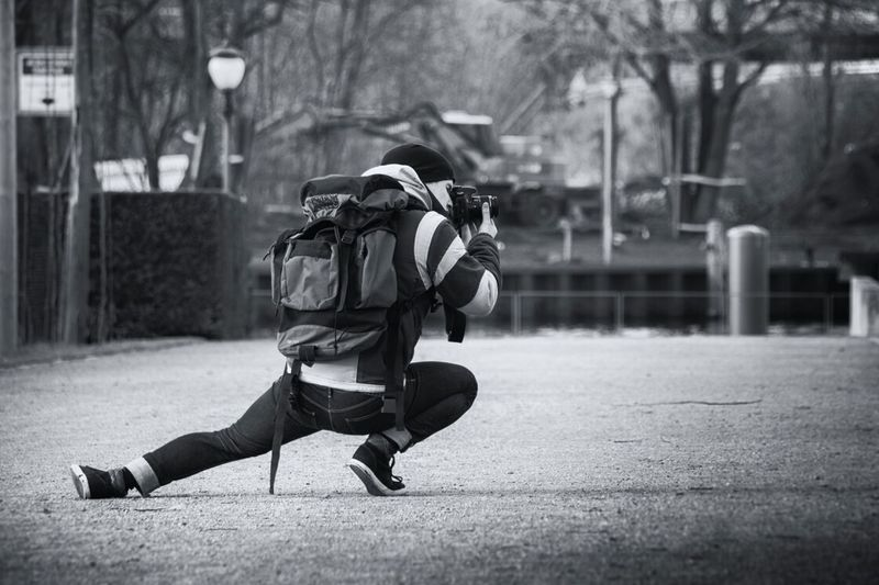 Full length of photographer photographing while crouching on street