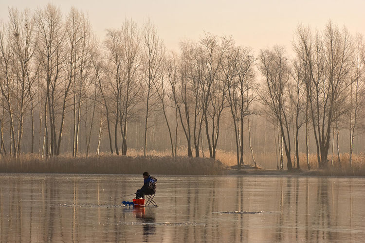 Side view of man fishing on frozen lake against bare trees