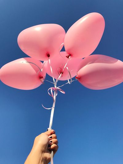 Low angle view of cropped hand holding balloons against clear blue sky
