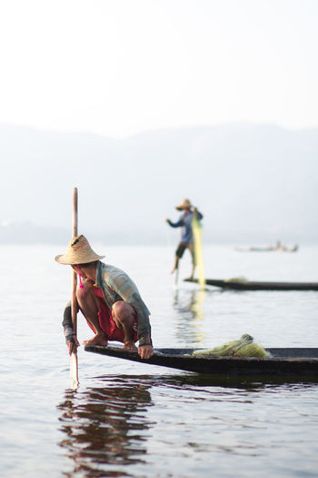 Intha fisherman on Inle Lake, Myanmar Beauty In Nature Clothing Day Fisherman Fishing Fishing Boat Inle Lake Lifestyles Men Myanmar Nature Nautical Vessel Oar Outdoors People Real People Rowing Sky Transportation Water Waterfront