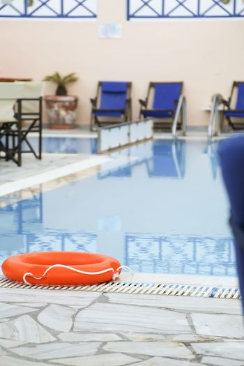 Close-up of chairs by swimming pool against building