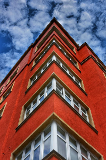 Low angle view of red building against cloudy sky