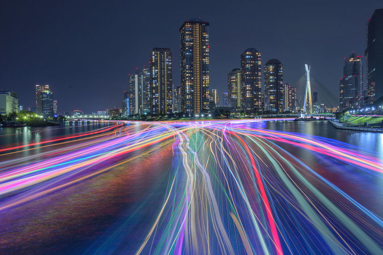 Light trails on road by illuminated buildings at night