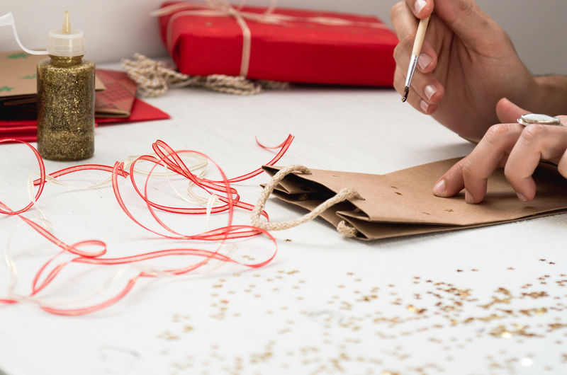 Cropped image of hand decorating paper bag on table