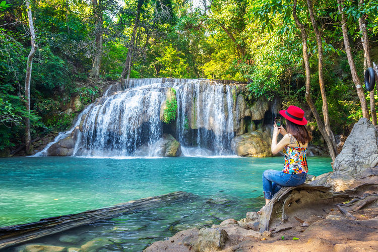 Woman sitting at Erawan waterfall in Thailand. Beautiful waterfall with emerald pool in nature. Tree Water Waterfall Plant Forest Motion Beauty In Nature One Person Scenics - Nature Nature Leisure Activity Land Flowing Water Full Length Blurred Motion Day Rock - Object Women Outdoors Rainforest