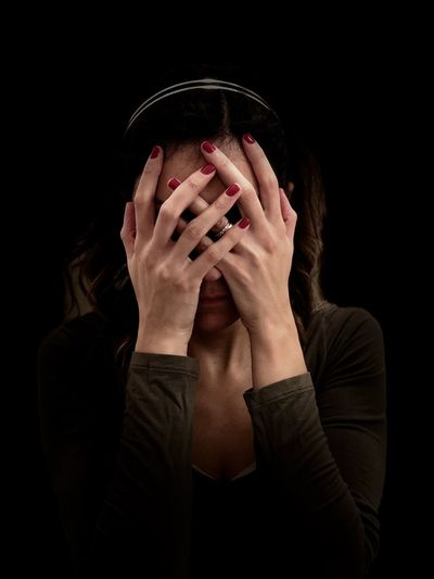 Depressed woman covering face against black background