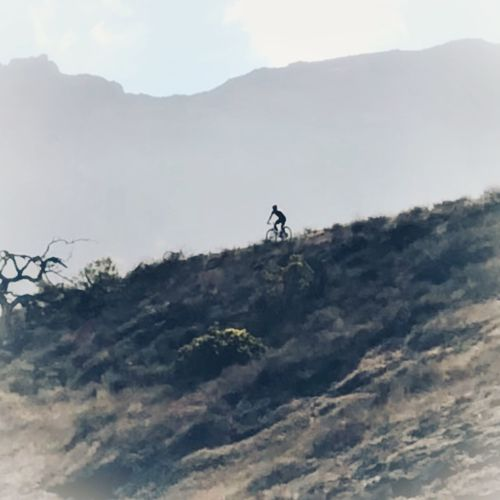 Man with umbrella on mountain range against sky